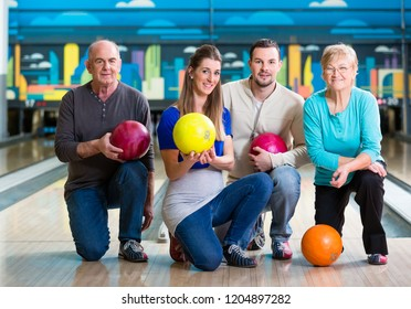 Happy family with multi colored bowling ball posing in alley