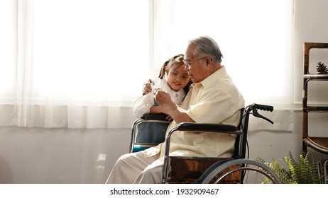 Happy Family Multi-generation daughter taking care of the senior father in the house, sitting on the wheelchair happiness, Elderly retirement concept.