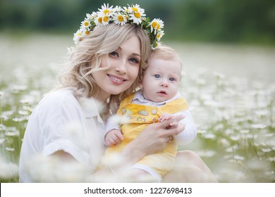 happy family in nature. woman with baby having fun in chamomile field