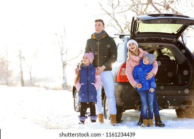 Happy family near car outdoors during snowfall. Winter vacation