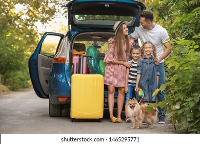 Happy family near car with packed luggage outdoors