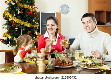 happy family near Christmas tree  over celebratory table  at home