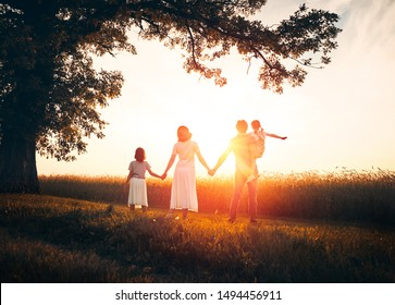Happy family on autumn walk! Mother, father and daughters walking in the Park and enjoying the beautiful autumn nature.