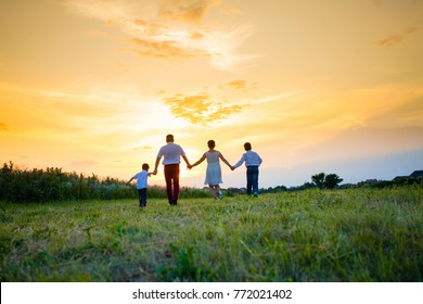 Happy family on the background of the sunset