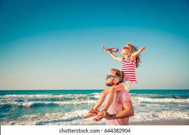 Happy family on the beach. People having fun on summer vacation. Father and child against blue sea and sky background. Holiday travel concept