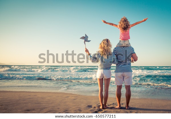 Happy family on the beach. People having fun on summer vacation. Father, mother and child against blue sea and sky background. Holiday travel concept