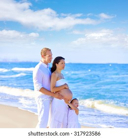 Happy family on the beach posing relaxed with pregnant mother woman