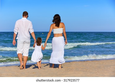 Happy family on the beach sand walking rear back view in summer
