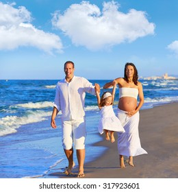 Happy family on the beach sand walking with pregnant mother woman