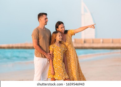 Happy family on the beach at summer vacation in Dubai, UAE. United Arab Emirates famous tourist destination.