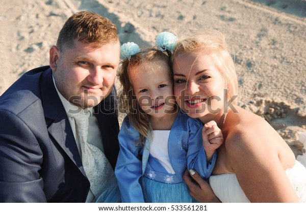 Happy family on a beach at sunrise - child mother and father