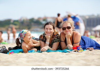 Happy family on the beach. Two pretty young women and a little girl child is lying on the beach. Selective focus.