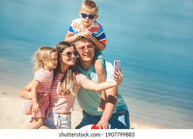 Happy family on the beach. Family vacation. People making selfie on cell phone