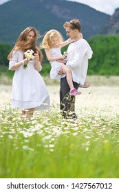Happy family on big camomile mountain meadow. Emotional, love and care scene.