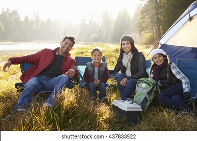 Happy family on a camping trip sit by tent looking to camera