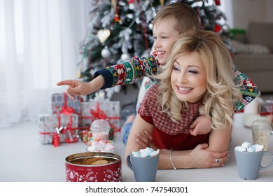 happy family on christmas time.mother with son drinking tea or cacao with marshmallows. woman with child having fun with cups and cookies by christmas tree and presents