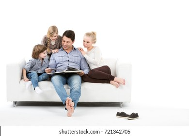 Happy family on the couch read the book together isolated on white background.