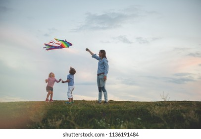 Happy family on the field. Mother and kids playing with a kite while running on meadow, sunset, in summer day. Funny family time. Happy little childs launch a kite with mum.
