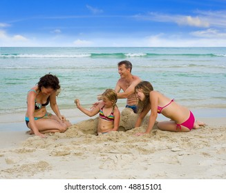 happy family on holidays playing at the beach, throwing sand at each other
