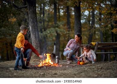 Fröhliche Familie auf Picknick im Wald bei Lagerfeuer