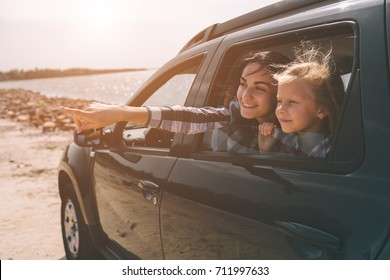 Happy family on a road trip in their car. Dad, mom and daughter are traveling by the sea or the ocean or the river. Summer ride by automobile