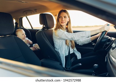 Happy family on the road, happy young mother with her baby traveling in her car