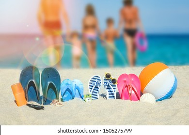 happy family on the sea with slippers on nature background