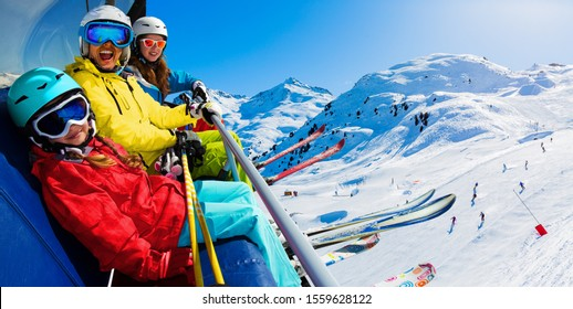 Happy family on ski lift enjoying winter vacations in mountains, Meribel, 3 Valleys, France. Playing with snow and sun in high mountains. Winter holidays.