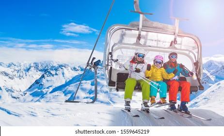 Fröhliche Familie auf Skilift Sessel genießen Winterurlaub in den Bergen Playing mit Schnee und Sonne in hohen Bergen. Winterferien.