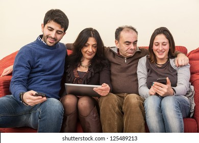 Happy Family on the Sofa with Electonic Devices