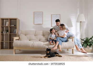 Happy family on sofa and puppy in living room