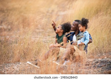 Happy family on summer sitting in the mountain meadow father and two daughters enjoying the outdoors beautiful nature sunset.