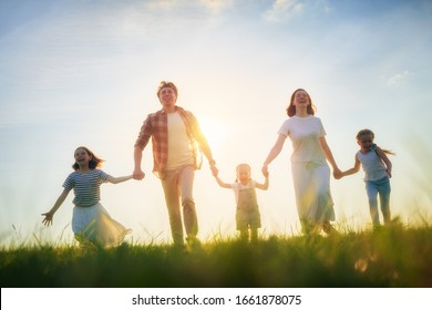 Happy family on summer walk! Mother, father and daughters walking in the Park and enjoying the beautiful nature.