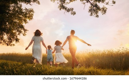 Happy family on summer walk! Mother, father and daughters walking in the Park and enjoying the beautiful nature. - Shutterstock ID 1679644186