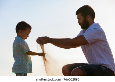 Happy family on sunset sea beach. Father, baby son play with sand slipping through man hand fingers. Child catching falling sand. Active parents, people outdoor activity on summer vacations with kids.