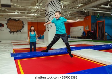happy family on a trampoline of mother and a child boy is jumping and playing on a trampoline in sport center