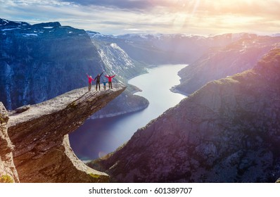 Happy Family On Trolltunga - View On Norway Mountain Landscape At Sunset From Trolltunga - The Troll's tongue in Odda, Ringedalsvatnet Lake, Norway.