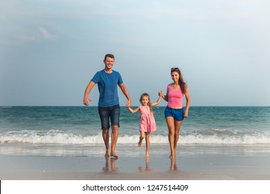 Happy family on vacation. Mom, Dad and a little daughter are walking along the seashore. Traveling family