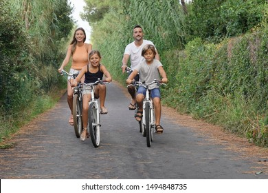 Happy family on vacation riding bikes