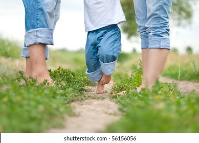 Happy Family on a Walk in Summer. Child with Parents Together. Feet Barefoot on Green Grass. Healthy Lifestyle. Dad Mom and Son. Spring Time