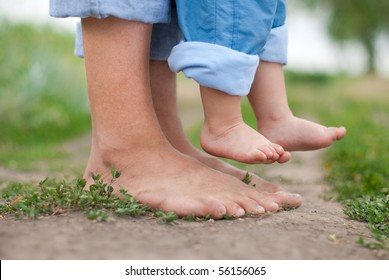 Happy Family on a Walk in Summer. Child with Father Together. Feet Barefoot on Green Grass. Healthy Lifestyle. Dad and Son. Spring Time