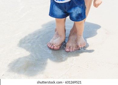 Happy Family on a Walk in Summer. Cute little Asian 1 year old toddler baby boy child with Father. Feet Barefoot on sand at the beautiful beach in Asia. Healthy Lifestyle. Dad and Son. Selective focus