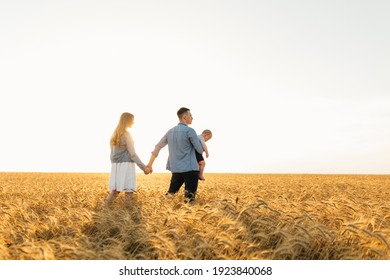 Happy family on wheat field at sunset having a great time together in nature