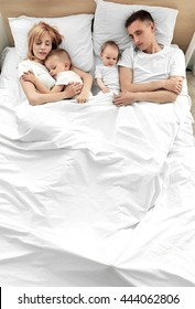Happy family on white bed in bedroom