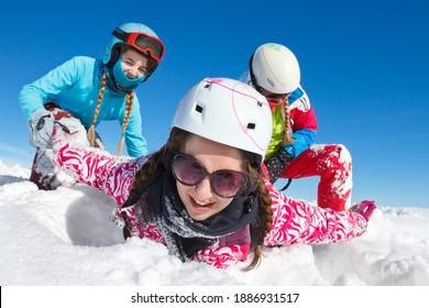 Bonne famille en vacances d'hiver avec ciel bleu et vêtements colorés jouant dans la neige fraîche sur les pistes de haute savoie