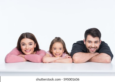 Happy family with one child leaning on table and smiling isolated on white