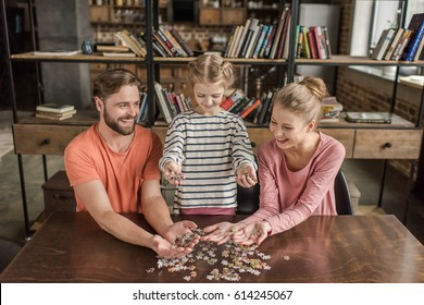 Happy family with one child playing with puzzles at home