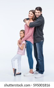 Happy family with one child standing together and hugging isolated on white