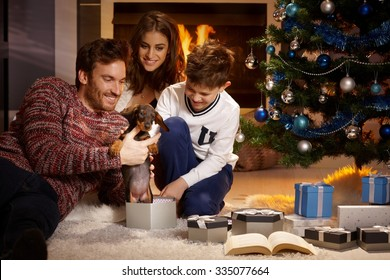 Happy family opening christmas box, holding puppy, all smiling.