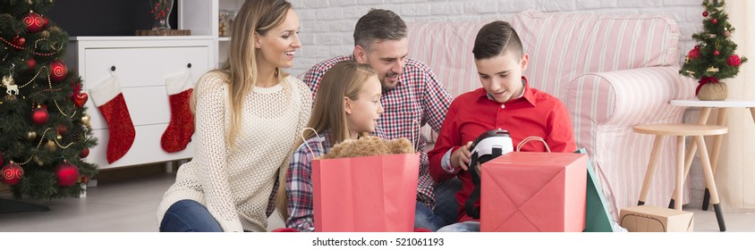 Happy family opening together christmas presents in the morning